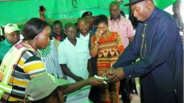 President Goodluck Jonathan receives his voting credentials at a polling station in Otuoke, Bayelsa state, 28 March 2015