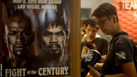 A customer checks boxing gloves signed by Manny Pacquiao on sale at a store in Manila