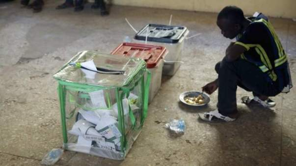 An elector worker eats his launch next to ballot boxes in a poling station in Kano - 28 March 2015