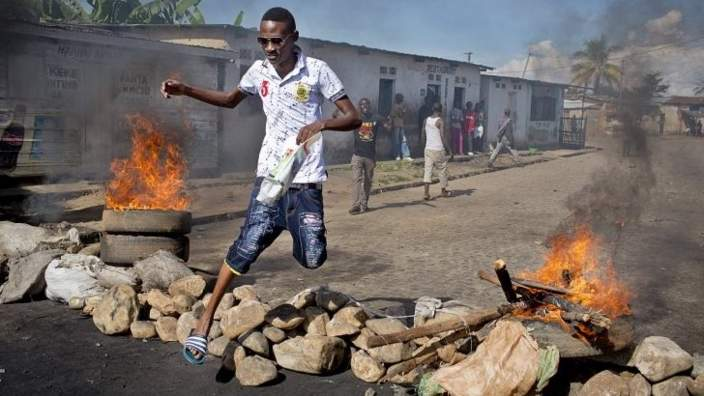 Civilian jumps over a burning barricade of rocks erected by residents to protect themselves from police, in a northern district of the capital Bujumbura, in Burundi Thursday 14 May 2015