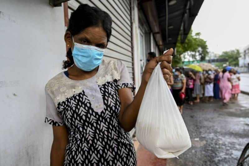Woman shows her food packet while others behind her wait in queue