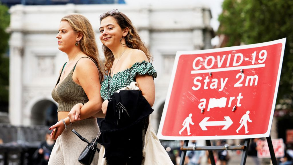 Two women walk past a Covid-19 warning sign in London