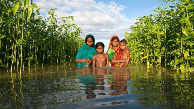 Family in floodwater in Bangladesh