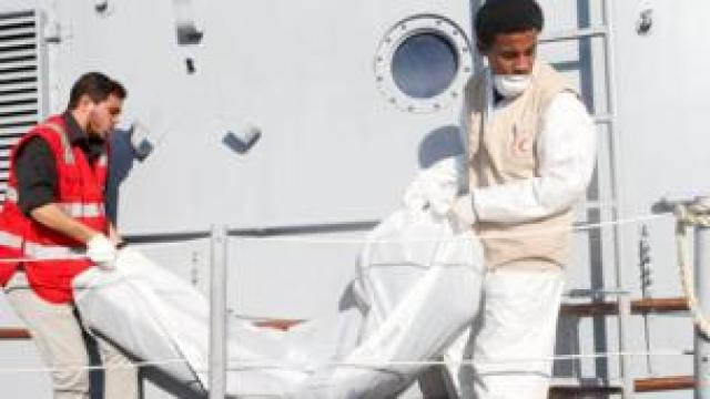 Libyan Red Crescent workers carry a bag containing a body of a migrant who died when a boat sank off Libya