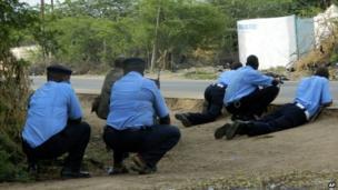 Kenyan police officers take cover outside the Garissa University College during an attack by gunmen in Garissa, Kenya, 2 April 2015