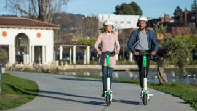 Two people riding Lime Scooters