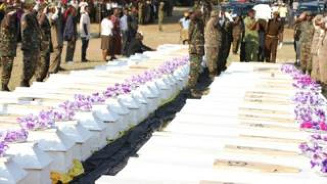 Military men saluting at line of coffins