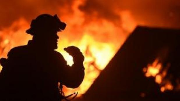 A firefighter drinks water in front of a burning house near Oroville, California (09 July 2017)