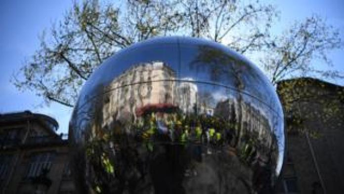 Demonstrators are reflected in a sculpture during yellow vest protest in Paris