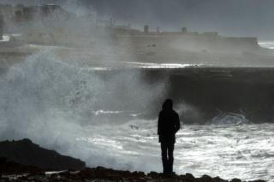 A Moroccan man walks along the coast during a storm in Rabat on January 8, 2018. Morocco has been facing an unusual cold wave for the past few days, with heavy snowfall in the mountainous regions and the installation of an anti-cold device in the most affected areas.