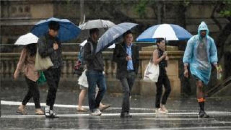 Pedestrians hold umbrellas as they walk in heavy rain in Sydney's central business district on 17 January 2020.