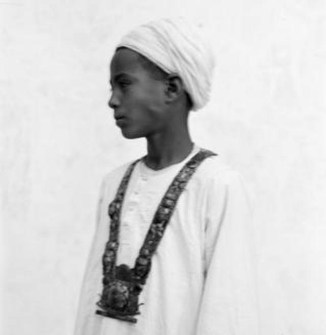 Blurred photograph of boy wearing gold necklace artefact