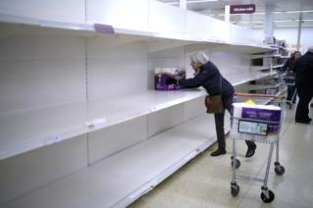 A senior citizen gets the last pack of toilet rolls at Sainsbury's Supermarket in Northwich, United Kingdom