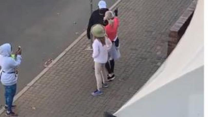 One person taking a picture of three people