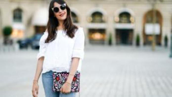 Fashion blogger Sarah Benziane wears a New Look white lace off-shoulder top and New Look jeans in Paris