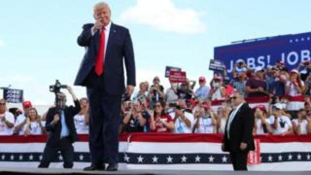 US President Donald Trump gestures in front of supporters at Basler Flight Service in Oshkosh, Wisconsin, US.