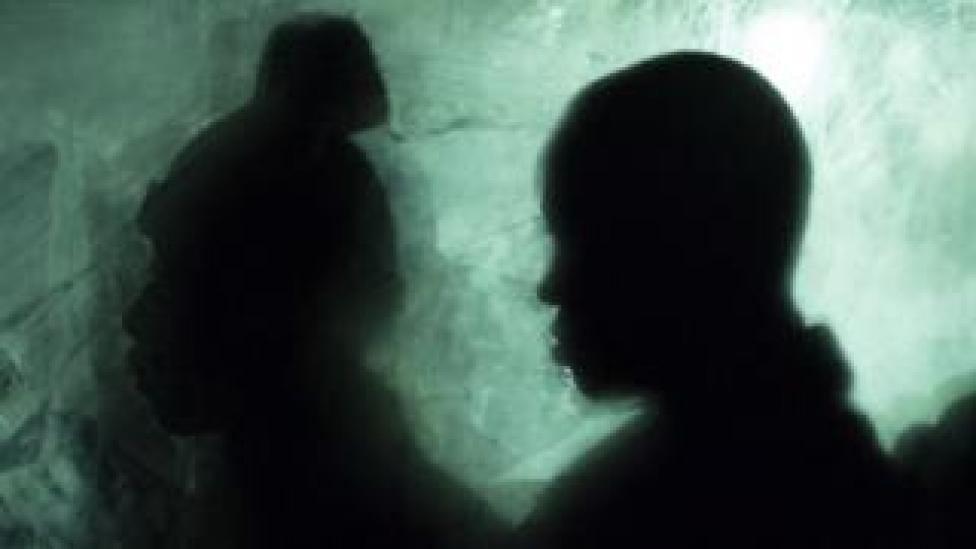 Silhouettes of two people in a bus waiting to be transferred