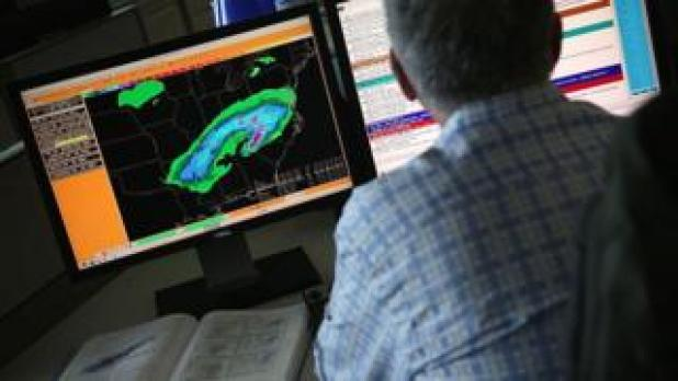 A US National Weather Service employee at work in front of computer screens showing weather data