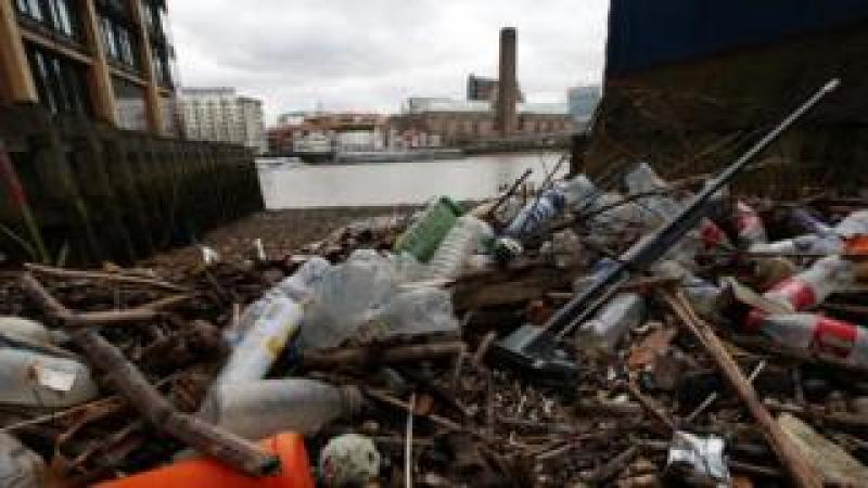 Plastic bottles and other waste littering the foreshore of the River Thames at Queenhithe Dock in London.