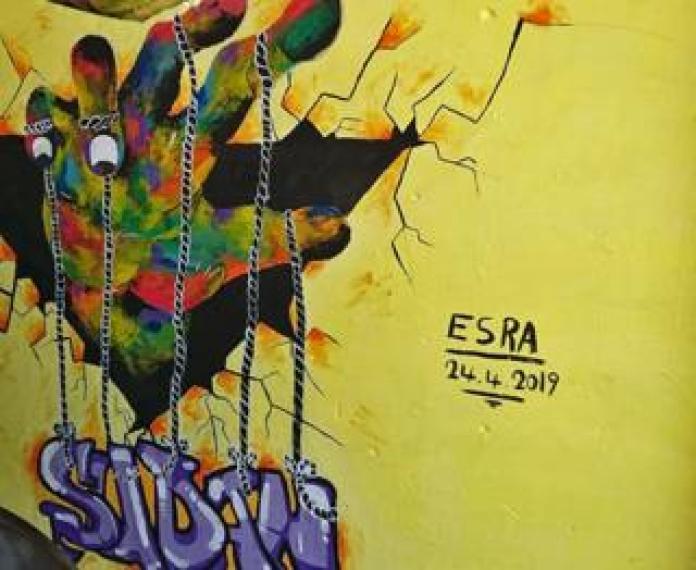 A mural showing a hand manipulating Sudan like a puppet - Kharotum, Sudan
