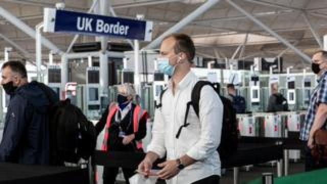 A passenger wearing a face covering approaches passport control at Stansted airport in Essex on 20 July