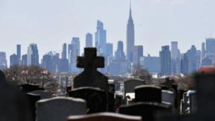 Gravestones of a cemetery are seen with the Manhattan skyline