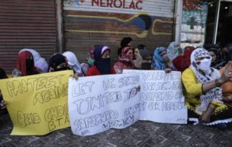 "Kashmiri Muslim women hold signs protesting against ""braid chopping"""