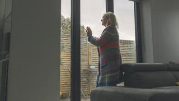 Woman looking out of her window