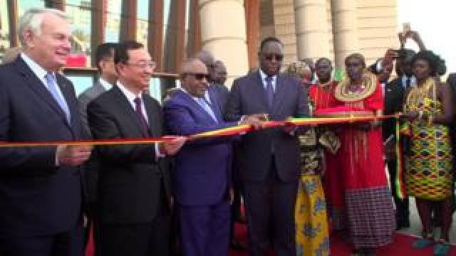 Senegal's President Macky Sall cuts a ceremonial ribbon to inagurate the museum