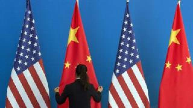 A woman sets up Chinese and US flags in Beijing, 2014
