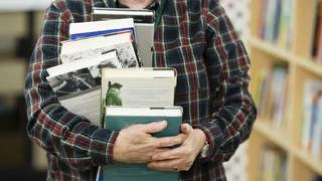 A man carrying a pile of books.