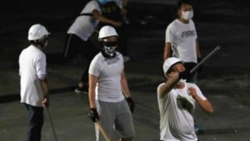 Masked men in white T-shirts, armed with sticks, after they attacked anti-extradition bill protestors after a demonstration. Yuen Long, Hong Kong