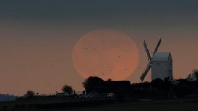 The full moon seen rising behind a windmill on the Sussex downs