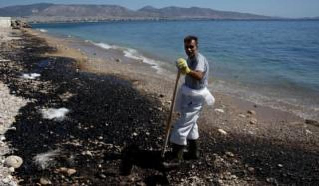 A clean-up worker struggles to remove an oil spill from a beach on the coast around Athens, Greece, on 13 September 2017.