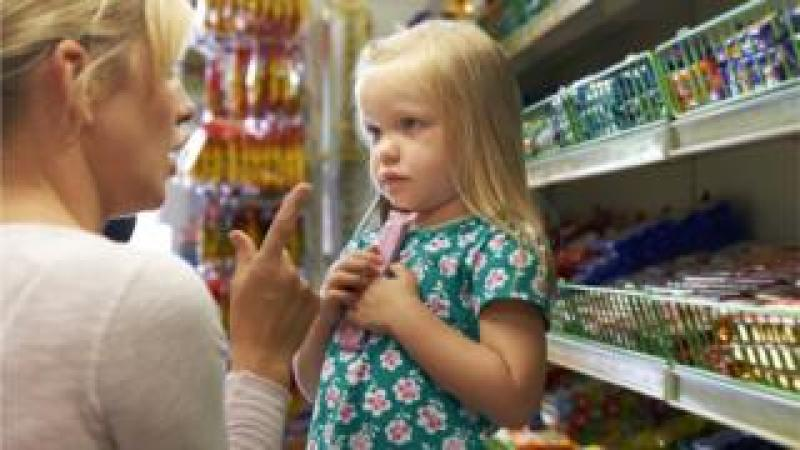 A child picking up chocolate from a supermarket shelf