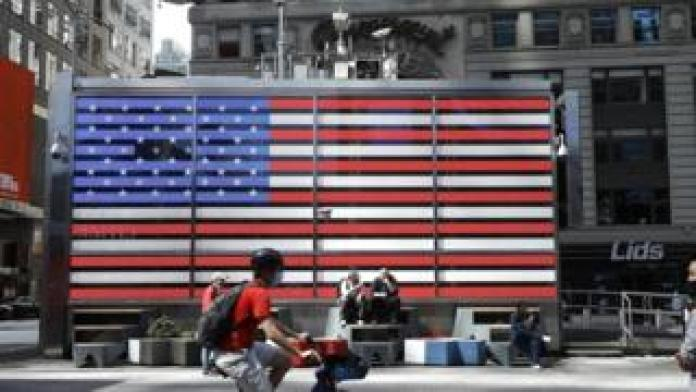 People are seen by the American flag in Times Square on May 22 in New York