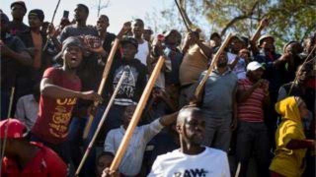 A group of Zulu men residing at the Jeppe Hostel shout and wave stick during a speech given by the Police Minister General Bheki Cele in JeppesTown, on September 3 in Johannesburg, 2019