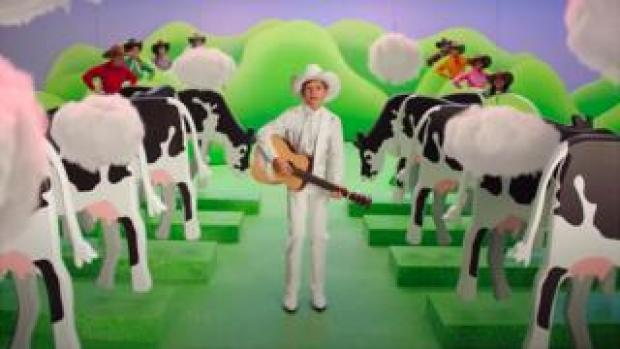 A boy wearing a cowboy hat sings about cow flatulence in a Burger King ad