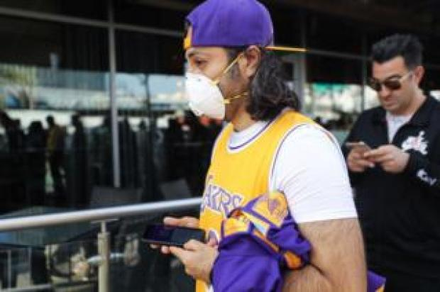 A Kobe Bryant fan wears a mask to his memorial service in LA on Monday