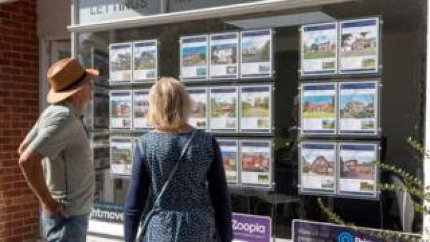 Couple looking at properties in estate agent window