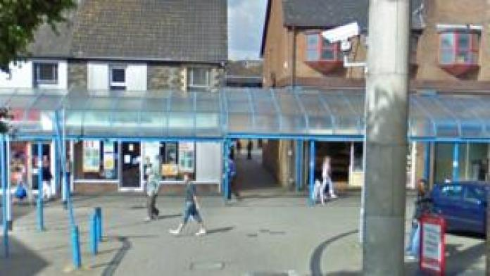 A view of Google Street from Forge Road - we can see a lot of shops and an alley