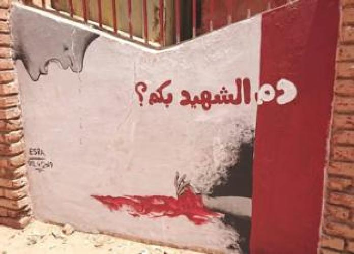 """A mural showing a person crying over a bleeding hand with the words: """"What is martyrs' blood worth?"""" - Khartoum, Sudan"""