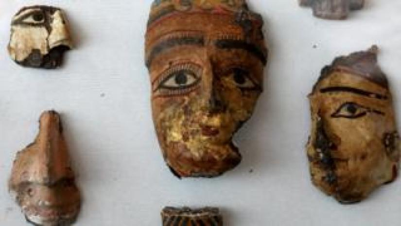 Painted segments of decorative faces on display at the tomb