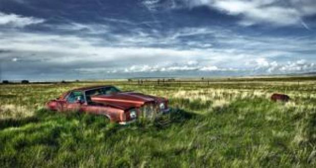 Cars: An abandoned car in an open field