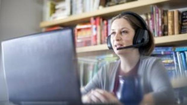 Stock image of woman with headset working at home