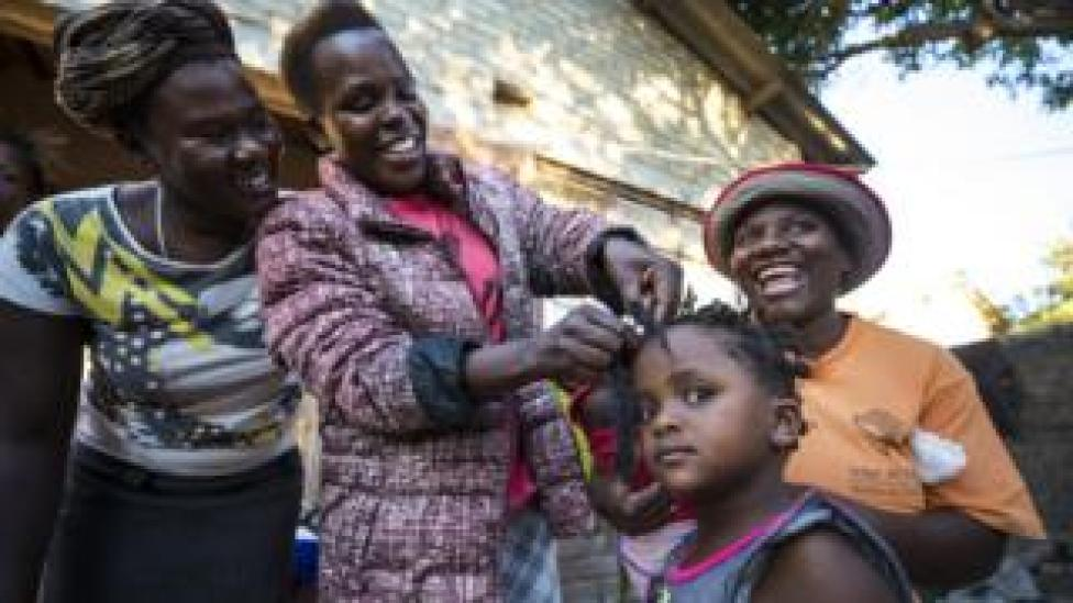 Woman plaits a little girl's hair whilst two other women look on