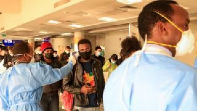 Passengers wearing face masks queue to be screened after arriving from China at Jomo Kenyatta International Airport