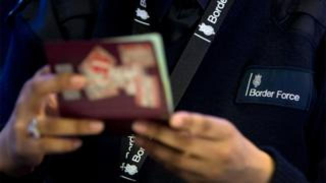 File image of a Border Force officer checking passports at Heathrow Airport
