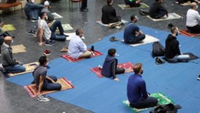 बर्लिन के एक चर्च में शुक्रवार की प्रार्थना के दौरान उपासक अपनी प्रार्थना मैट पर बैठते हैं