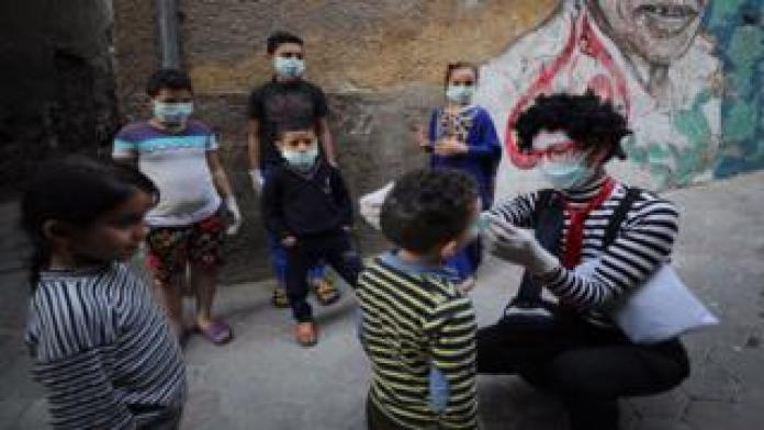 Egyptian clown Ahmed Naser wearing a face mask helps children to put on face masks